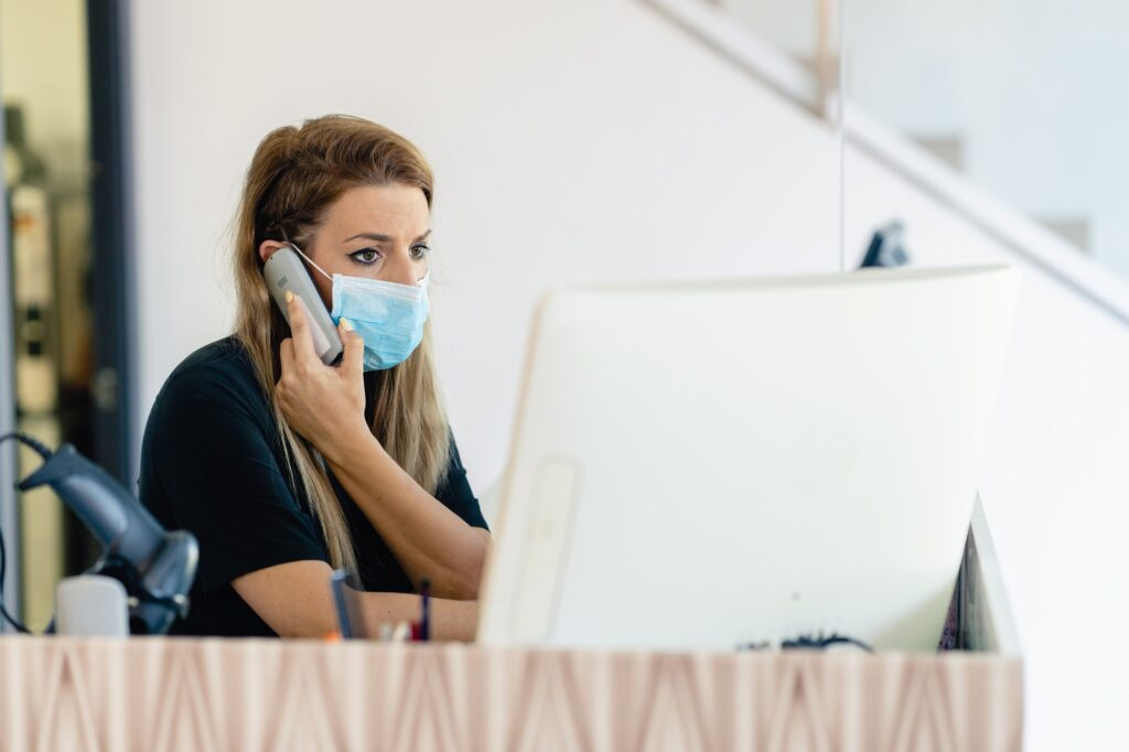 Female hairdresser answering the phone to give her clients an appointment, wearing a protective mask